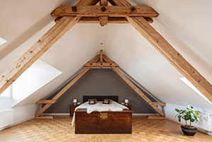 32309372 - interior of a loft or dormer bedroom in the apex of a roof with visible timber roof trusses , a patterned parquet floor and double bed